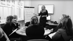 Staff meeting, woman presenting with flip chart